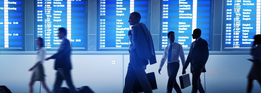 business people in front of flight information screens