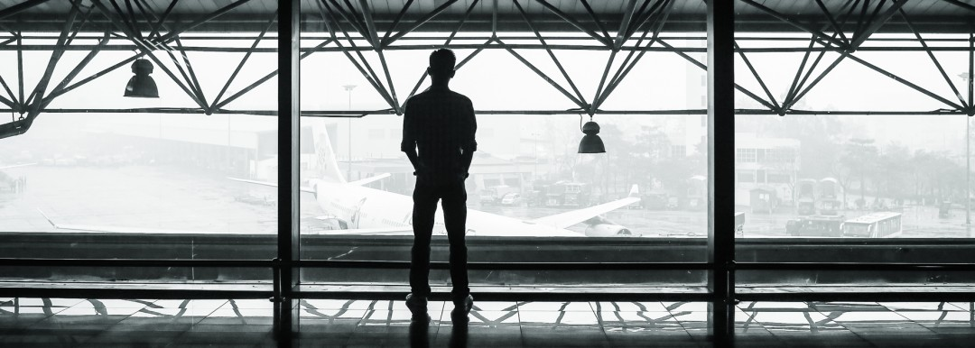 person looking out of window in airport